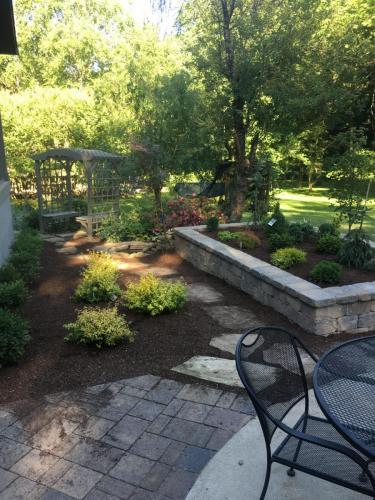 Backyard pavers, raised bed and shrubs